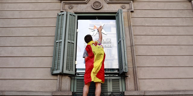 A youth draped in a Spanish flag puts a sticker on a building in Barcelona, Spain, Oct. 29, 2017.
