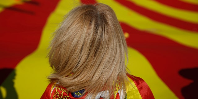 A woman draped in a Spanish flag stands by a giant Catalan flag before a rally against Catalonia's bid to secede.
