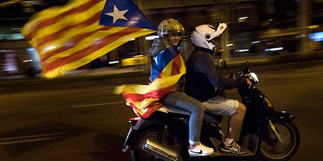 A woman holds a Catalan independence flag on a motorcycle after taking part in a protest against the National Court's decision to jail civil society leaders without bail in Barcelona, Spain.