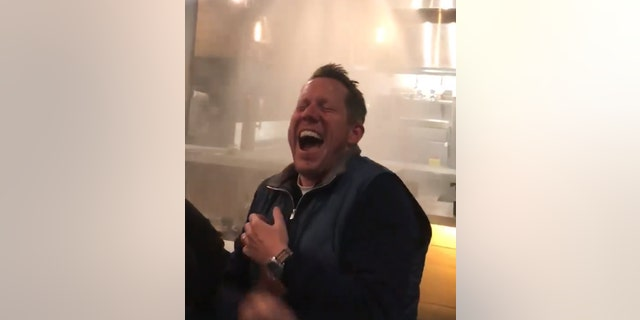The large group of diners couldn't stop laughing after watching the sprinklers soak down the waitstaff.