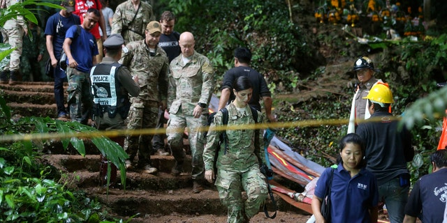 U.S. Special Operations Command Pacific Search and Rescue team personnel walk out of a cave where a young soccer team and their coach are believed to be missing in northern Thailand.