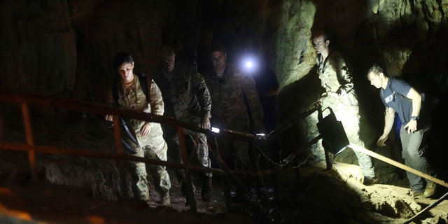 U.S. Special Operations Command Pacific Search and Rescue team personnel walk in a cave where a young soccer team and their coach are believed to be missing.