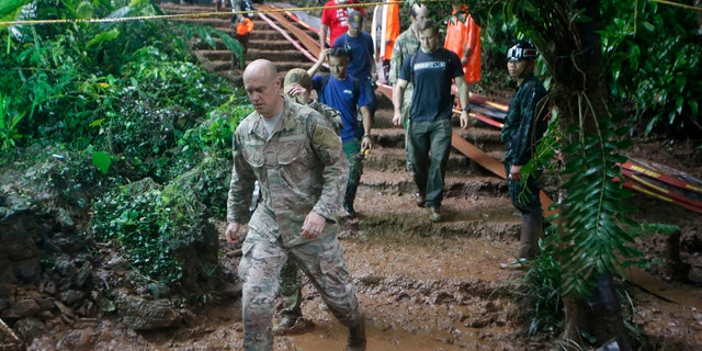 U.S. Special Operations Command Pacific Search and Rescue team personne; walk out of a cave where young soccer team and their coach are believed to be missing, Thursday, June 28, 2018, in Mae Sai, Chiang Rai province, in northern Thailand.