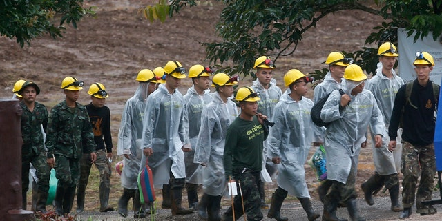 Rescuers walk toward the entrance to a cave complex where five were still trapped, in Mae Sai, Chiang Rai province, northern Thailand Tuesday, July 10, 2018.