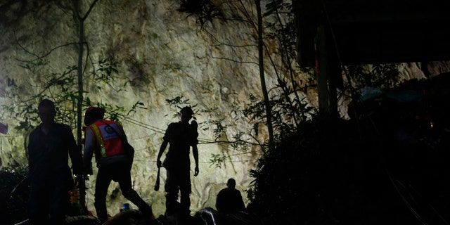 Rescuers make their way down at the entrance to a cave complex where 12 boys and their soccer coach went missing, in Mae Sai, Chiang Rai province, in northern Thailand.