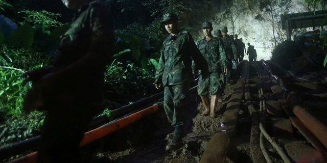 Rescuers make their way down at the entrance to a cave complex where 12 boys and their soccer coach went missing, in Mae Sai, Chiang Rai province, in northern Thailand, Sunday, July 1, 2018.