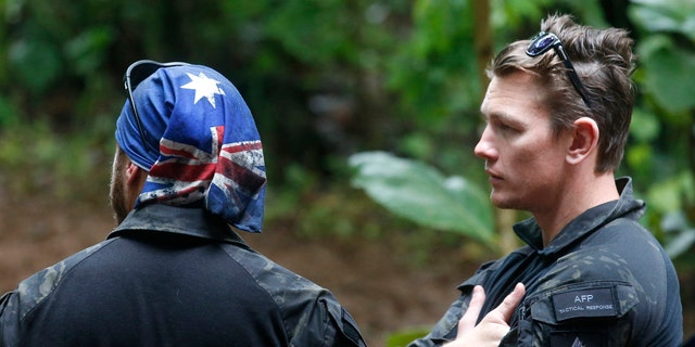 Australian Federal Police and Defense Force personnel talk each other near a cave complex where 12 boys and their soccer coach went missing, in Mae Sai, Chiang Rai province, in northern Thailand, Sunday, July 1, 2018.