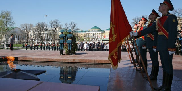 Russian President Vladimir Putin, in the background, takes part in a wreath laying ceremony at the Tomb of Unknown Soldier on the eve of the Victory Day in Moscow, Wednesday, May 8, 2013. President Vladimir Putin attended a ceremony ahead of two days of public holiday and military parades for Victory Day, which remains a significant event on the Russian calendar. (AP Photo/RIA-Novosti, Yekaterina Shtukina, Government Press Service)