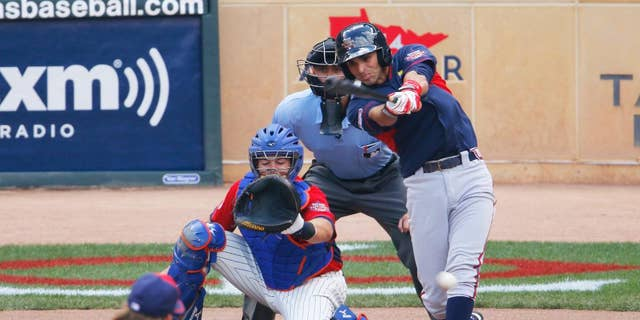 World's Jose Peraza, right, singles during the first inning of the All-Star Futures baseball game in front of United States' catcher Kevin Plawecki, Sunday, July 13, 2014, in Minneapolis. (AP Photo/Paul Sancya)