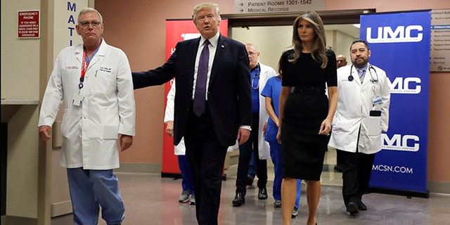 President Donald Trump and first lady Melania Trump walk with surgeon Dr. John Fildes at the University Medical Center after meeting with victims of the mass shooting Wednesday, Oct. 4, 2017, in Las Vegas.