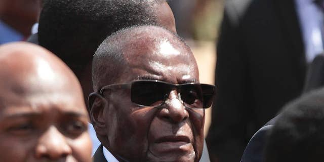 FILE -  In this April 12, 2017 file photo, Zimbabwean President Robert Mugabe, centre, attends the burial of a former liberation war hero in Harare, Zimababwe. Mugabe is denying his country is in a fragile state and insists it is one of Africa's most developed despite its plunging economy. The 93-year-old was speaking Thursday, May 4, 2017 at the Africa leg of the World Economic Forum. (AP Photo/Tsvangirayi Mukwazhi, File)