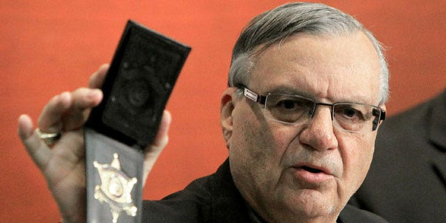 December 21, 2011: Maricopa County Sheriff Joe Arpaio shows his badge as he holds a ceremony where 92 of his immigration jail officers, who lost their federal power to check whether inmates are in the county illegally, turn in their credentials after federal officials pulled the Sheriff's office immigration enforcement powers in Phoenix.