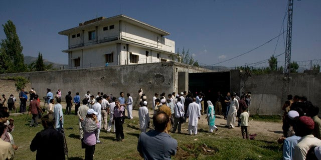 Local people and media gather outside the perimeter wall and sealed gate into the compound and a house where al-Qaida leader Osama bin Laden was caught and killed late Monday, in Abbottabad, Pakistan, on Tuesday, May 3, 2011.  Local residents showed off small parts of what appeared to be a U.S. helicopter that Washington said malfunctioned and was disabled by the American commando strike team as they retreated, while Pakistan's leader on Tuesday denied suggestions that his country's security forces had sheltered Osama bin Laden. (AP Photo/Anjum Naveed)