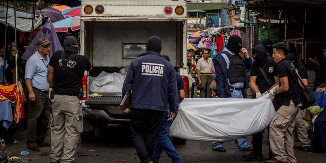 In March 15, 2017 file photo, police investigators carry a body to a forensic vehicle, after a shootout between private security guards and gang members, at the central market in San Salvador, El Salvador, Wednesday, March 15, 2017. The rate of violent death in El Salvador is still higher than all countries suffering armed conflict except for Syria.
