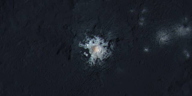 The bright central spots near the center of Occator Crater is shown in enhanced color in this view from NASA's Dawn spacecraft. Such views can be used to highlight subtle color differences on Ceres' surface. (NASA/JPL-Caltech/UCLA/MPS/DLR/IDA/PSI/LPI)