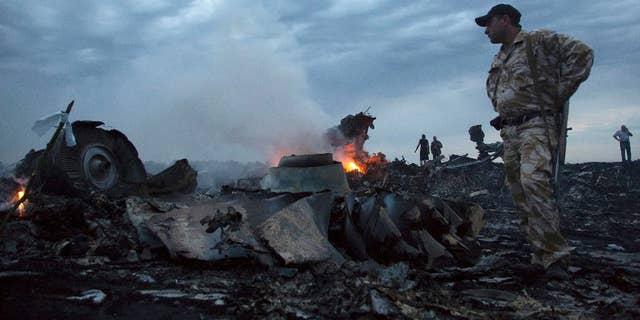 People walk amongst the debris at the crash site of a passenger plane near the village of Grabovo, Ukraine.