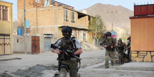 April 15: NATO soldiers run during a gun battle in Kabul, Afghanistan.
