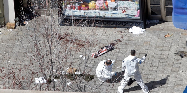 Two men in haz-mat suits investigate the scene of the first bombing on Boylston Street in Boston Tuesday, April 16, 2013 near the finish line of the 2013 Boston Marathon, a day after two blasts nearby killed three and injured over 170 people. (AP Photo/Elise Amendola)