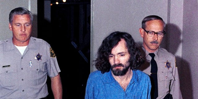 """FILE – In this Aug. 20, 1970, file photo, Charles Manson, head of the cultic """"Manson Family"""" charged with murder-conspiracy in the Tate-LaBianca slayings, is escorted by deputy sheriffs to court in Los Angeles. The AP reported Friday, June 23, 2017, that stories claiming Manson is dead or free on parole are false, with California corrections officials verifying Manson remains incarcerated. (AP Photo/File)"""