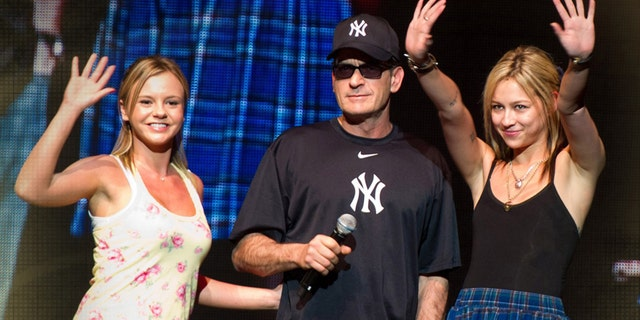"""Charlie Sheen (center) on stage with his """"Goddesses"""" Rachel Oberlin , aka Bree Olson (l) and Natalie Kenly (r), onstage during """"My Violent Torpedo of Truth/Defeat is Not An Option Show"""", Radio City Music Hall, New York, 2011."""