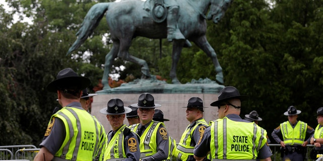 Virginia State Troopers stand beneath a statue of Robert E. Lee prior to a white supremacist rally.