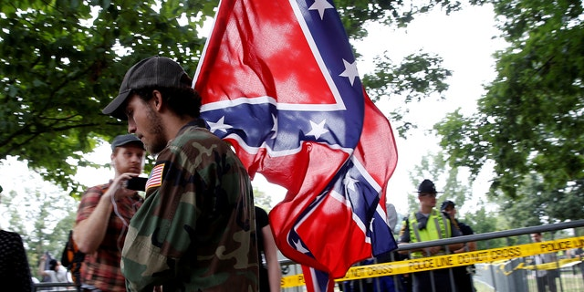 A white supremacists carries the Confederate flag as he arrives for a rally in Charlottesville, Virginia, U.S., August 12, 2017.   REUTERS/Joshua Roberts - RTS1BI7C