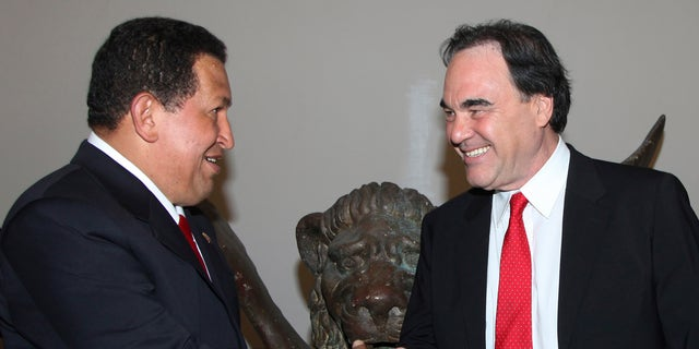 """Venezuela's President Hugo Chavez (L) shakes hand with U.S. film director Oliver Stone during the """"South Of The Border """" premiere at the Sala Grande during the 66th Venice Film Festival September 7, 2009. REUTERS/Alessandro Bianchi   (ITALY ENTERTAINMENT POLITICS) - RTR27JTQ"""