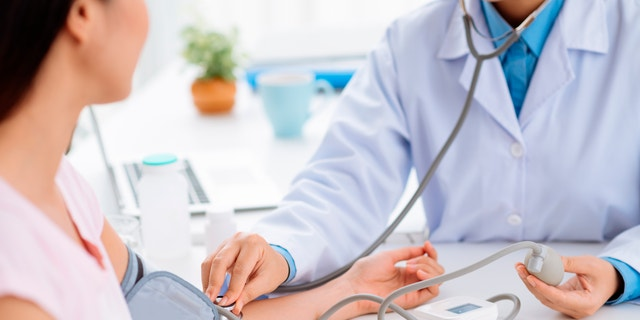 Doctor checking blood pressure of the patient, selective focus