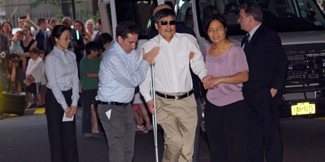 Blind Chinese dissident Chen Guangcheng (C) is helped by his wife Yuan Weijing (R) after arriving in New York May 19, 2012