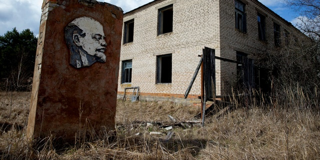 A panel with a portrait of Soviet state founder Vladimir Lenin and an abandoned building are seen at the 30 km (19 miles) exclusion zone around the Chernobyl nuclear reactor in the abandoned village of Orevichi, Belarus, March 12, 2016. (REUTERS/Vasily Fedosenko)
