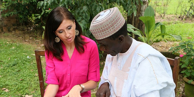 Kristin Wright and Yakubu Nkeki looking through photos of the missing Chibok girls in Jos, Nigeria in September of 2015.
