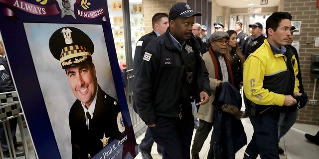 Chicago police officers pass a memorial portrait of Cmdr. Paul Bauer outside the Near North District headquarters, Feb. 14, 2018.