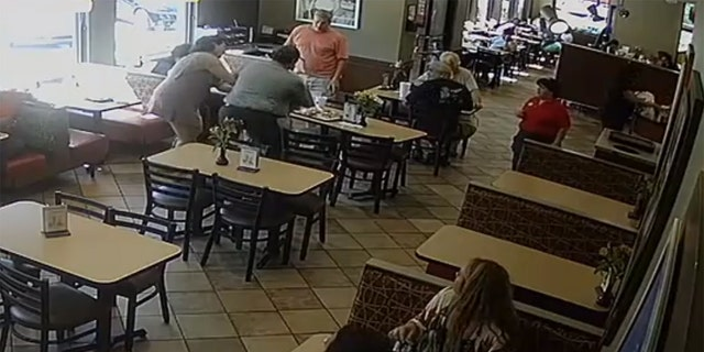 Harris, in gray, with his back to the security camera, rushed to the man's aid after a fellow employee alerted him to the situation in the dining area.