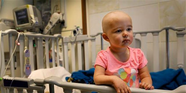 In this June 11, 2015 photo,Talia Pisano stands in her bed at Lurie Children's Hospital in Chicago. Talia is getting tough treatment for kidney cancer that spread to her brain. She's also getting a chance at having babies of her own someday. (AP Photo/Christian K. Lee)