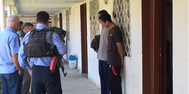 Mostafa Qais Ahmed Dawood and Awad Arkan Helal Mohammed stand solemnly outside followig their interrogation.