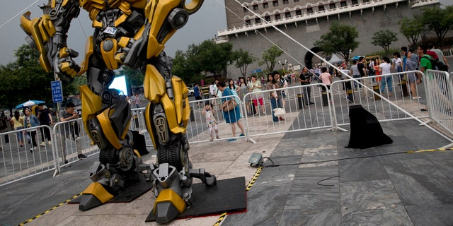 "June 21, 2014. A child stands on a barricade fence looks at a replica model of Transformers character Bumblebee on display in front of Qianmen Gate, as part of a promotion of the movie ""Transformers: Age of Extinction"" in Beijing, China."