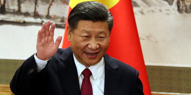 In this Oct. 25, 2017, file photo, Chinese President Xi Jinping waves while addressing the media as he introduced new members of the Politburo Standing Committee at Beijing's Great Hall of the People.