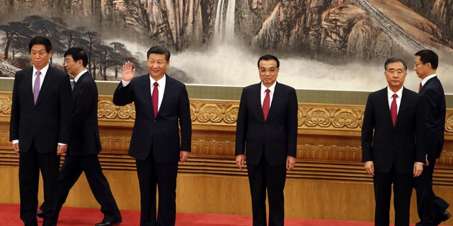 In this Oct 25, 2017, file photo, Chinese President Xi Jinping, third from left, waves near Chinese Premier Li Keqiang, third from right, as they walk in with other members of the Chinese Politburo Beijing's at the Great Hall of the People.