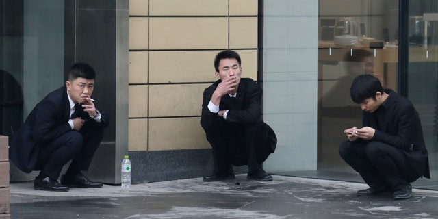 Employees smoke outside an office building in Beijing, November 25, 2014. REUTERS/Jason Lee