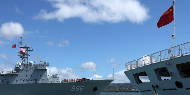 June 24, 2014: The Chinese People's Liberation Army (PLA) Navy replenishment ship Qiandaohu (866) (L) sails past the PLA Navy hospital ship, Peace Ark, as it docks at the Joint Base Pearl Harbor Hickam to participate in the multi-national military exercise RIMPAC 2014, in Honolulu, Hawaii.