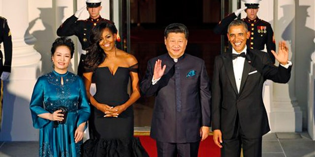 Sept. 25, 2015: President Barack Obama, right, and Chinese President Xi Jinping, second from right, wave along with, wives Peng Liyuan, left, and first lady Michelle Obama as they arrive for a state dinner at the White House in Washington.
