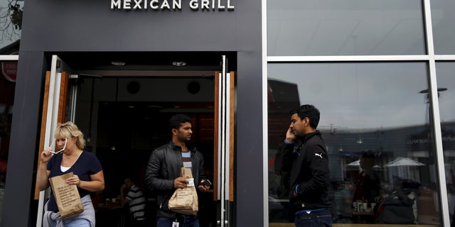 People carry bags as they leave a Chipotle Mexican Grill restaurant in San Francisco, California July 21, 2015. Burrito chain Chipotle Mexican Grill Inc reported lower-than-expected quarterly revenue on Tuesday. REUTERS/Robert Galbraith