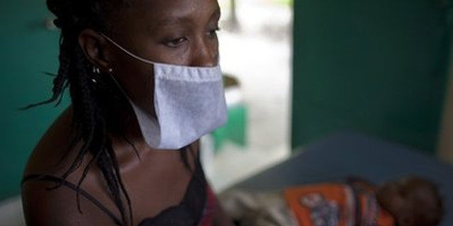 A woman waits with her son who suffers from cholera symptoms at the hospital in Archaie, Haiti, Tuesday Nov. 9, 2010. A confirmed case of cholera had never been seen in this Caribbean country before October and has killed at least 580 people and hospitalized thousands.