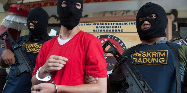 Indonesian police hold rifles while guarding recaptured U.S. citizen and inmate Christian Beasley, clad in red.