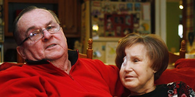 Bob Niles, left, puts his arm around his wife Karen Niles, right, in their home in Blackwell, Okla., in this photo taken Monday, Feb. 14, 2011. (AP)