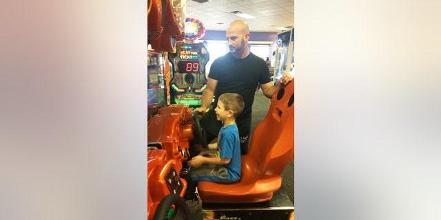 Austin Moniz, and his dad, Michael Moniz, enjoy playing a driving game during Sensory Sensitive Sunday at Chuck E. Cheese's.