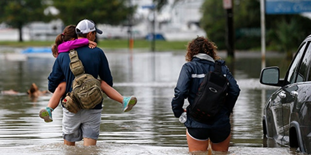 Don Noel carries his daughter Alexis with his wife Lauren as they walk through a flooded roadway to check on their boat in the West End section of New Orleans, June 21.