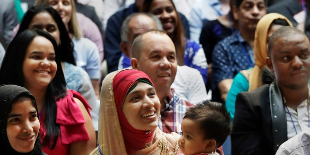 Mosammat Rasheda Akter, center, of Bangladesh, holds her seven-month-old daughter Fahmida during a naturalization ceremony, Tuesday, July 3, 2018, at the New York Public Library's Celeste Bartos Forum.