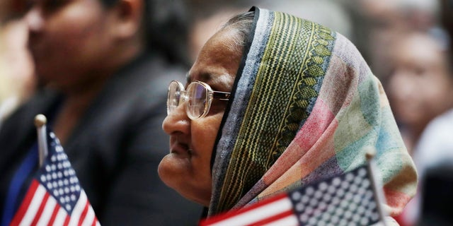 Hazera Khanom of Bangladesh listens during a naturalization ceremony, Tuesday, July 3, 2018, at the New York Public Library.