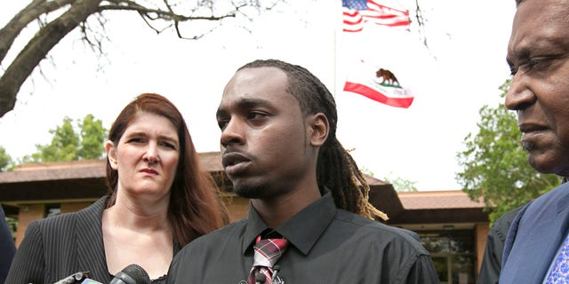 Nandi Cain, center, answers a reporters question concerning the alleged beating he received from a Sacramento Police officer two weeks ago during a news conference Monday, April 24, 2017, in Sacramento, Calif.